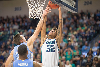 No. 32 John Bowen takes the ball toward the basket against two Tar Heel defenders.