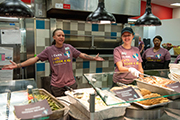 Behind the food service counter, one female Campus Dining employee spreads her arms in a welcoming manner while two others look on.