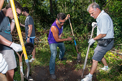 Chancellor, with shovel (right) and others dig in the Bluethenthal Wildflower Preserve.