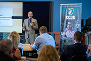 Steve Hunt speaks in front of a banner for the UNCW Center for Cyber Defense Education.