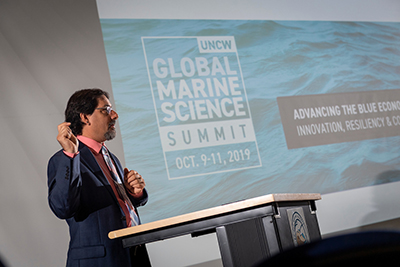 Chris Finelli in front of screen shot of the Global Marine Summit logo