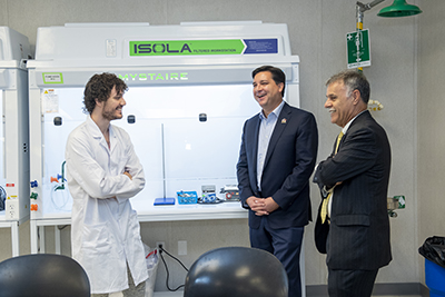 Graduate student (left) in one of the temporary labs, talks with Rep. David Rouzer (center) and Chancellor Sartarelli.