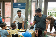 UNCW students work with young children around a table.