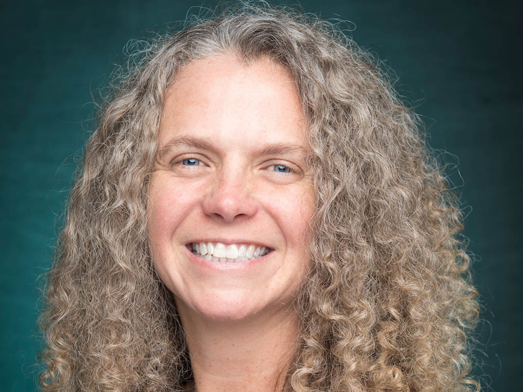 Faculty portrait of Andi Steele, smiling, against a teal background.