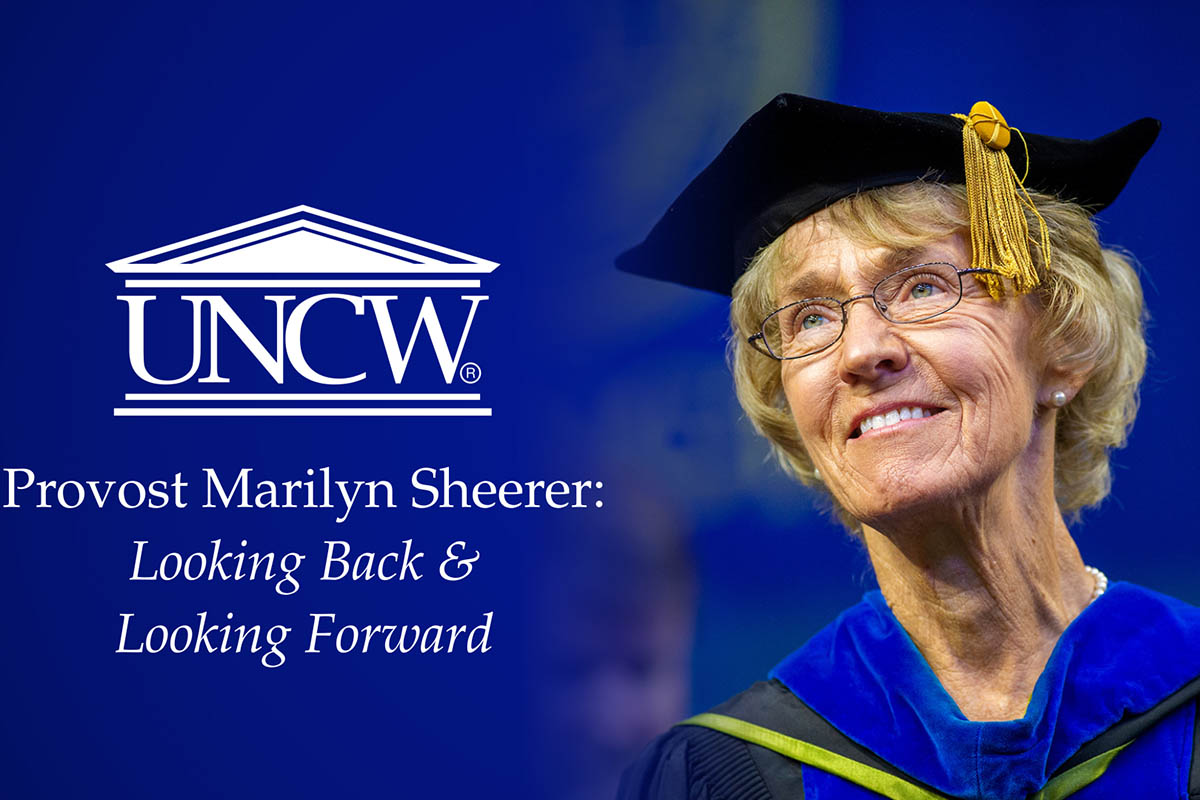 """Provost Sheerer in her academic regalia. Text at left (in white on blue background) is UNCW logo above """"Provost Marilyn Sheerer: Looking Back & Looking Forward"""