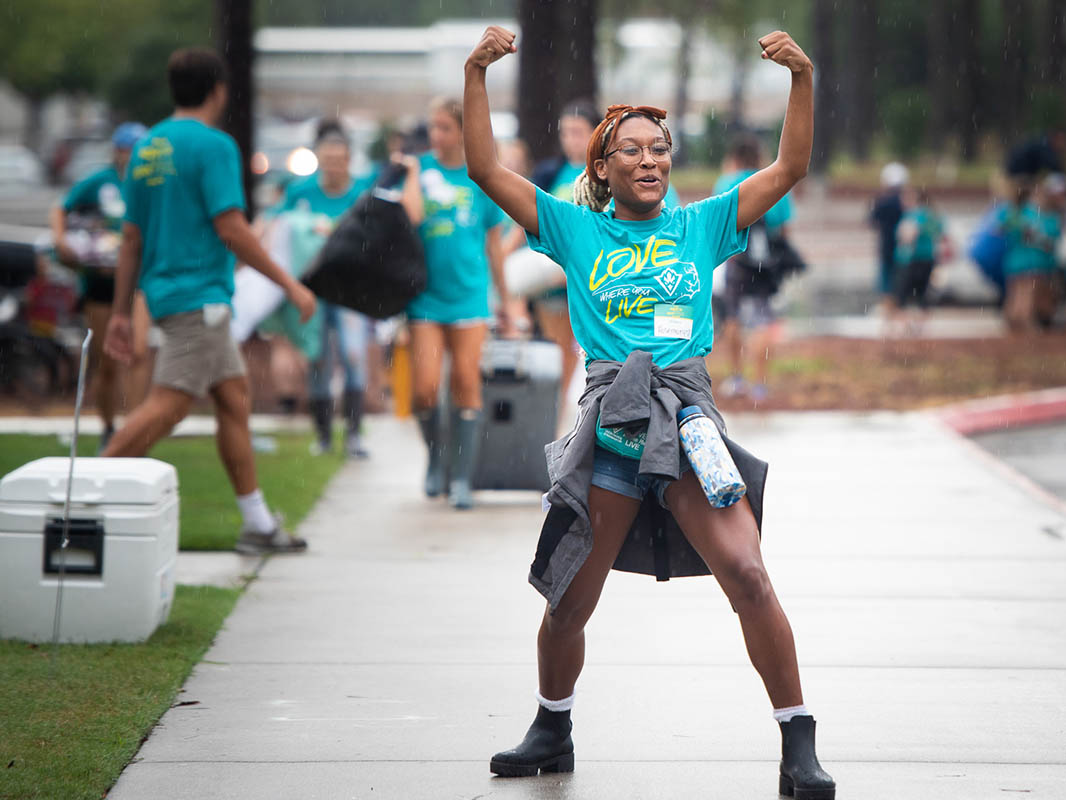 Rosemary Colen, dressed for Move-In 2019, with her rainjacket tied around her waist and a water bottle hanging from her waist, assumes a wide stance with arms raised and fists closed as though showing off her strength. Other Move-In volunteers are in the background.