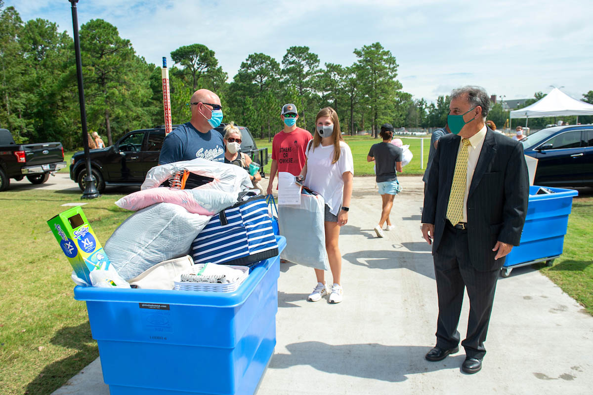 Chancellor Sartarelli (right, wearing a suit, tie and teal face covering) greets the parents of a new student during Move-In. The parents are also masked and are standing beside a large blue container filled with dorm essentials.