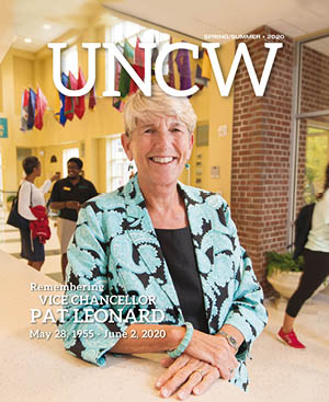 UNCW Magazine cover featuring Pat Leonard, leaning on a reception desk inside the Fisher Student Center.