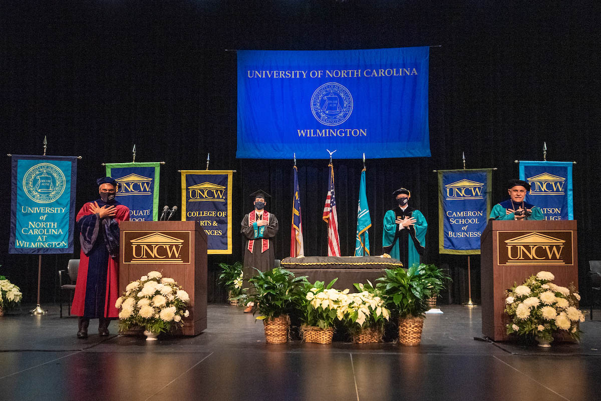 Pictured onstage (socially distanced) during Commencement 2020are Provost James J. Winebrake; Pietro Brucia'21, senior class president; UNCW Board of Trustees Chairman Henry L. Kitchin Jr.; and Chancellor Sartarelli.