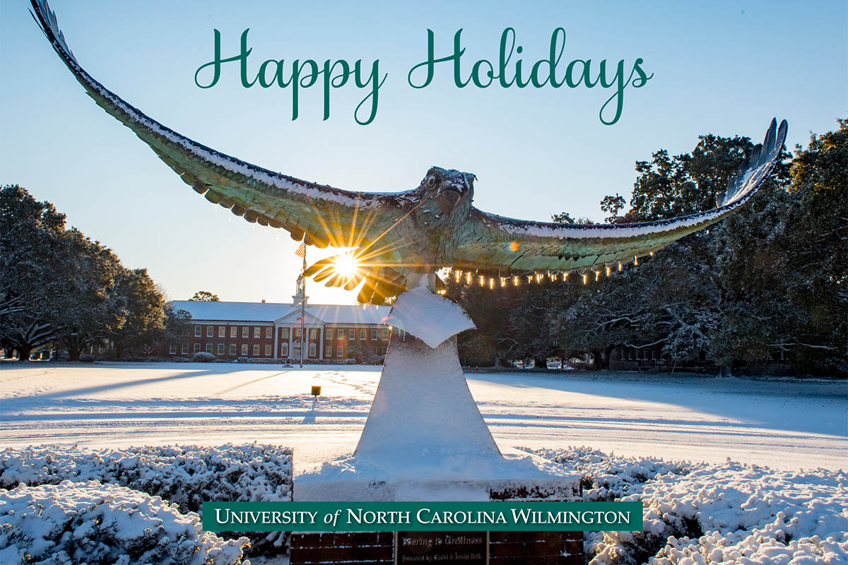 Soaring seahawk in front of a snow-covered Hoggard lawn, with Hoggard Hall in the background. Text: Happy Holidays.