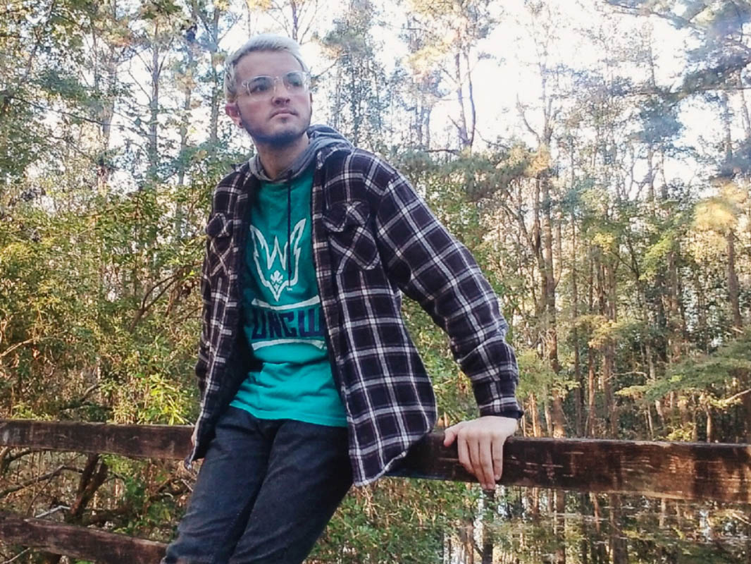 Brandon Yates leans agains the rail of a foot bridge with foliage in the background.
