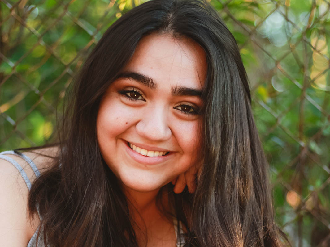 Isabella Galletto '20, close-up head shot, with foliage in the background.