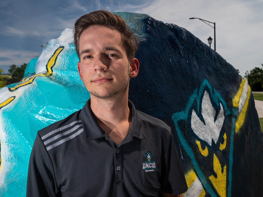Nick Pianovich stands in front of the spirit rock, painted teal with a Seahawk emblem.