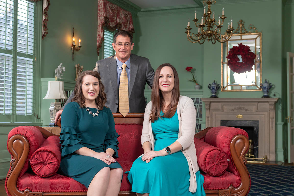 Two women seated side by side on an antique sofa covered in red and a man standing between the two behind the sofa. Left to right, Young Alumna of the Year Julie Andrews '13; retired Seahawk baseball Coach Mark Scalf '80, Distinguished Alumnus of the Year; and Ashlee Balena'95, Distinguished Citizen of the Year.