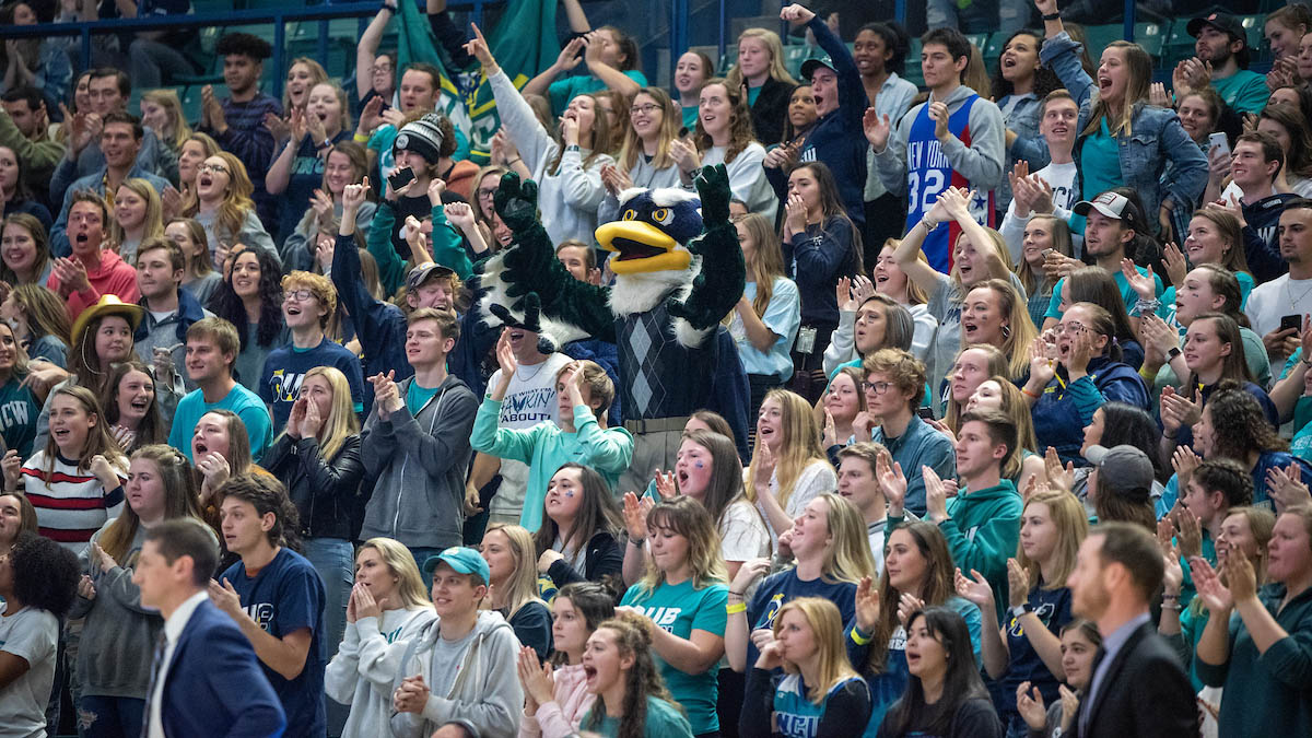 Sammy C. Hawk is in the middle of a cheering crowed of students at the Homecoming men's basketball game.