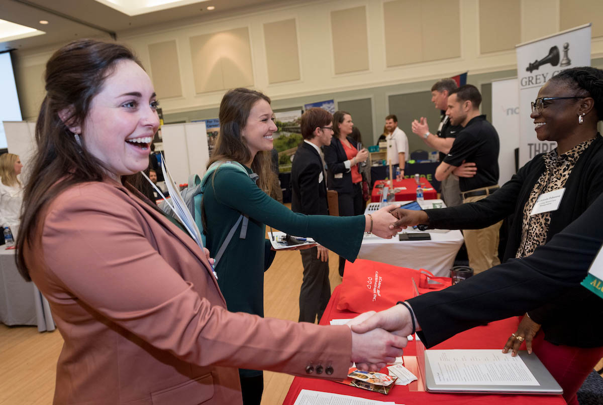 Students dressed in business attire on one side of a series of tables shake hands with representatives of local businesses and organizations across the tables.