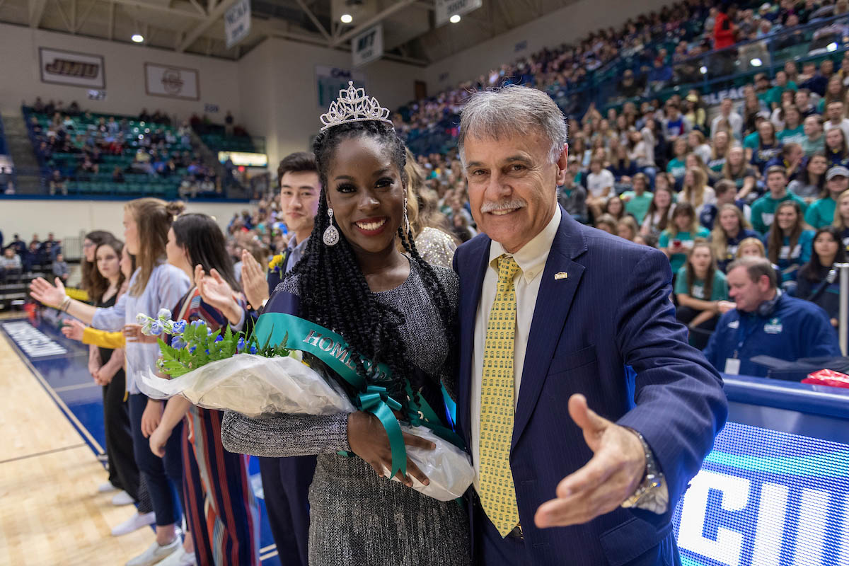 Homecoming Queen Ricki Nelson (left, wearing a tiara and sash and holding a bouquet of flowers) and Chancellor Sartarelli stand courtside at the men's basketball game in Trask, with a crowd in the stands.