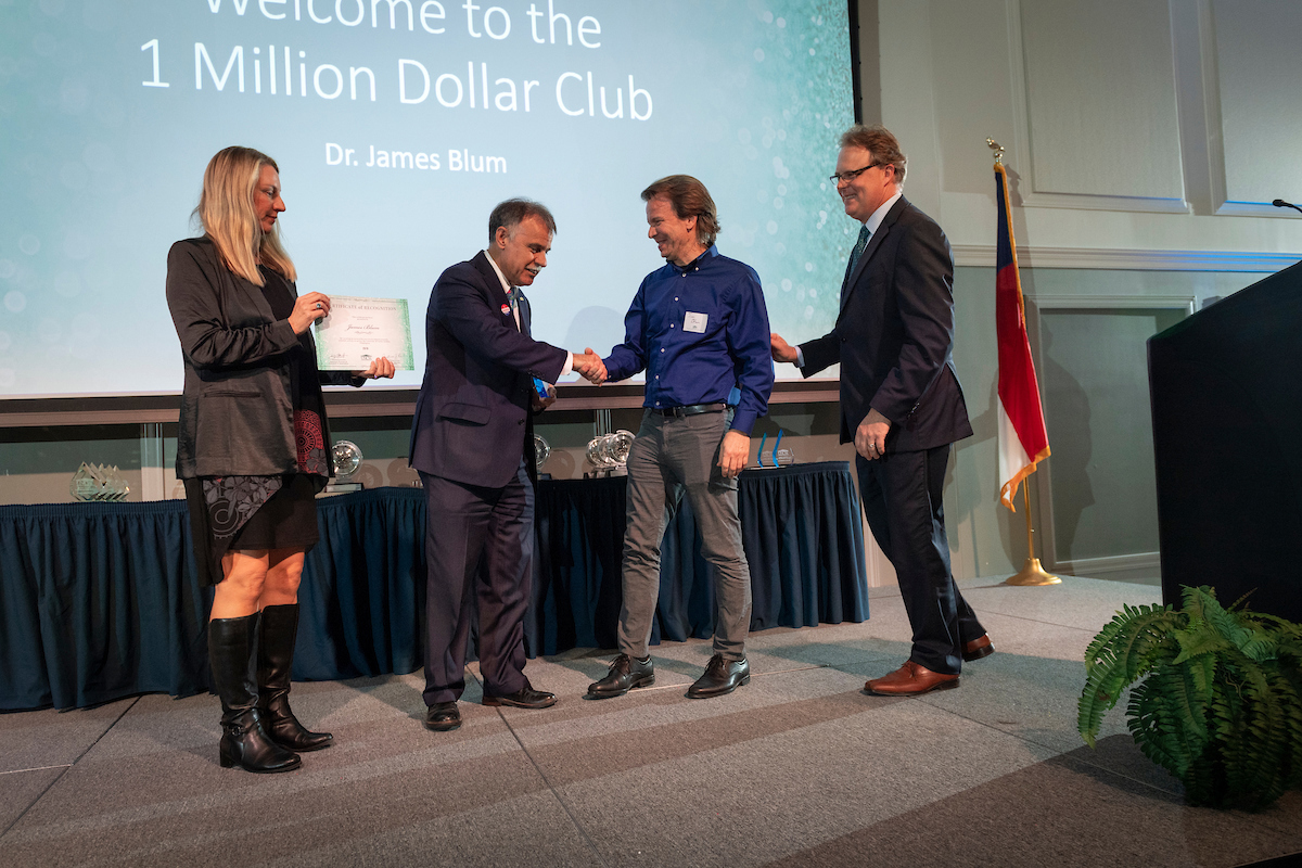 Justine Reel (left); Chancellor shaking hands with James Blum (second from right); Stuart Borrett. They are in frong of a large screen naming new members of the Million Dollar Club.