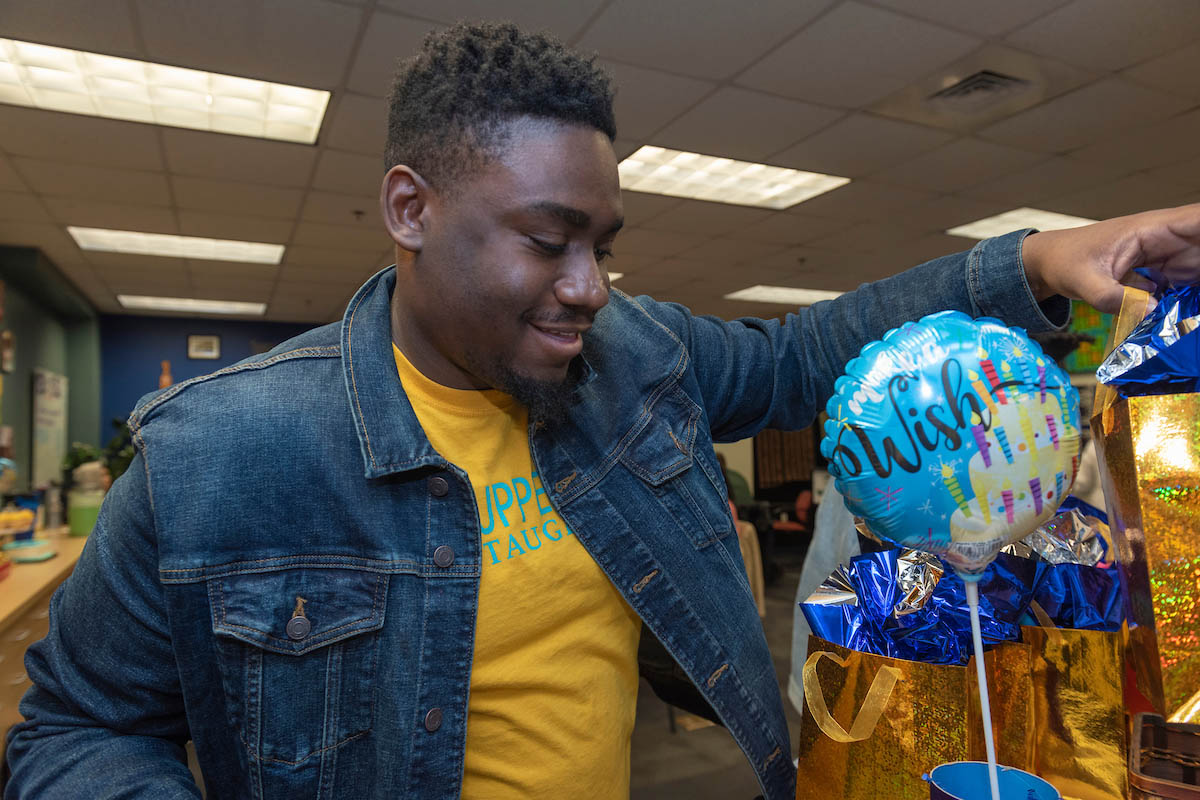 Manny Lloyd in a denim jacket and yellow shirt stand in front of a birthday balloon and colorful packages in the Upperman Center.