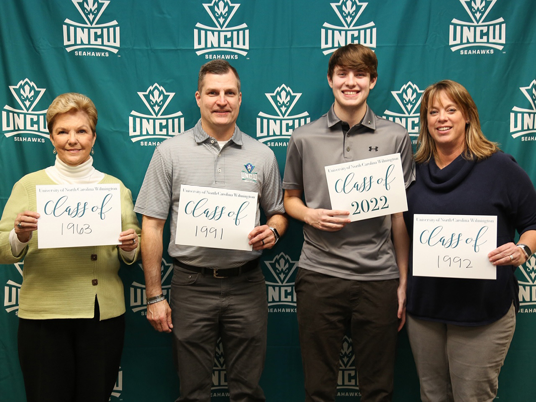 Holding up signs with their graduation years in front of a teal curtain with the Seahawk logo repeated over and over: Left to right, Judy Matthews Russell, Jay Russell, Gavin Russell and Dawn England Russell.