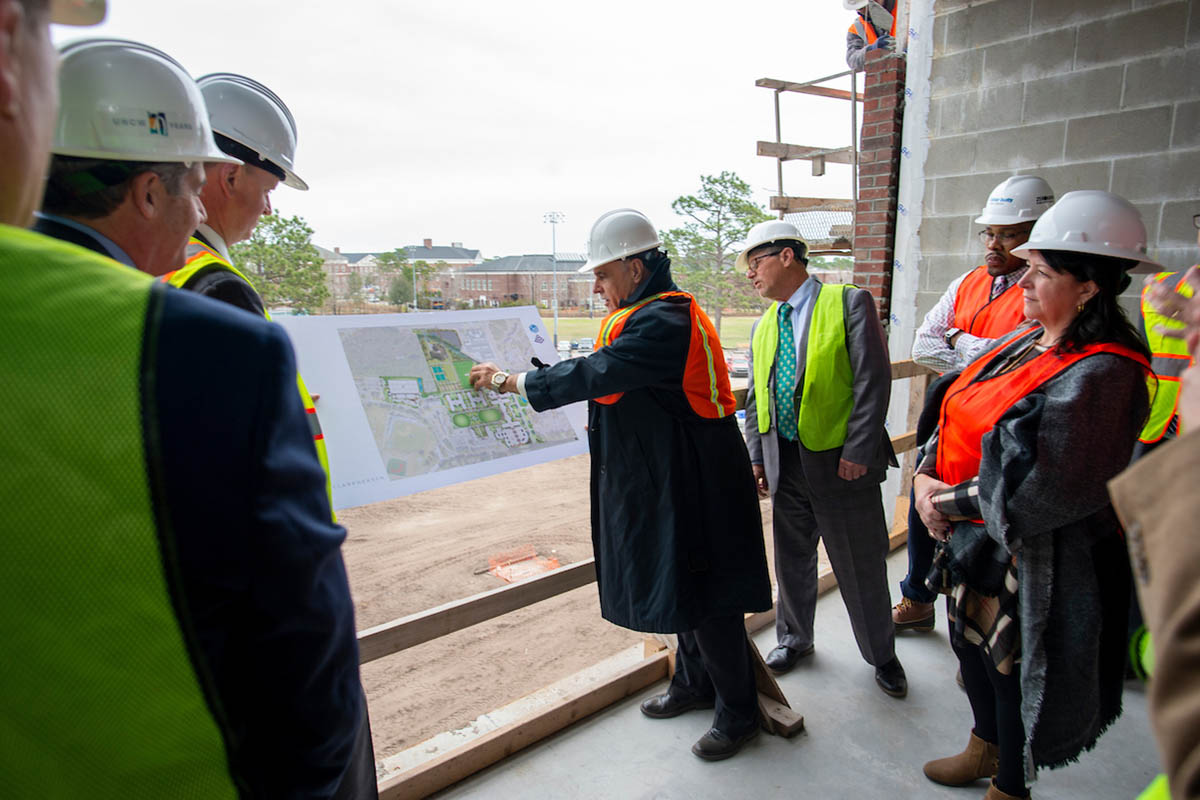 Chancellor Satarelli, center, sideways from the camera and wearing a vest and hard hat, points to a drawing showing new green space and the location of a future dining hall. Male and female members of the BOT, also in vests and hard hats look on while inside one of the new residence halls under construction.