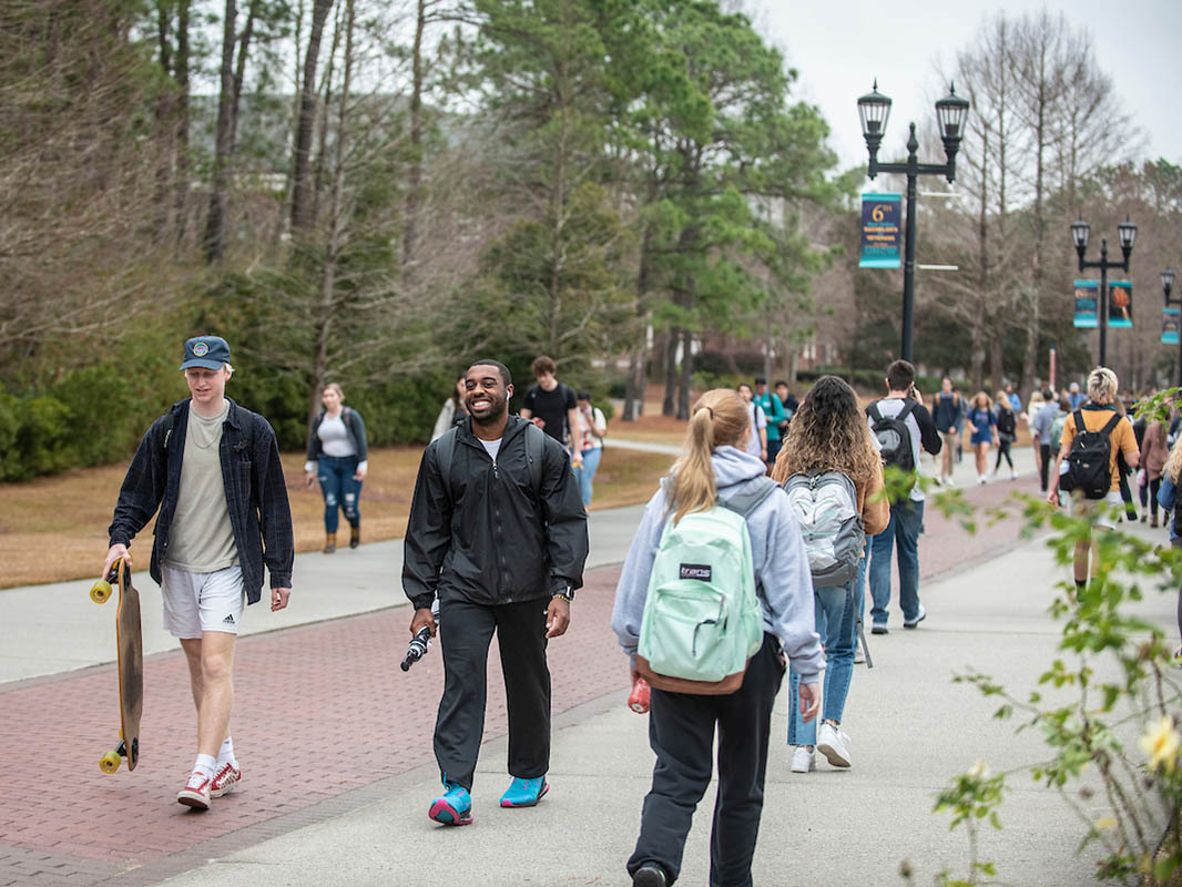 Students on Chancellor's Walk. In the foreground are a man carrying a skateboard, one carrying an umbrella and a student with a backback whose back is turned to the camera.