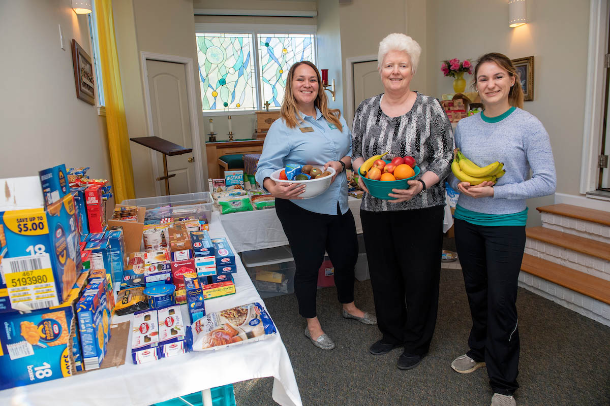 Left to right: Jaime Russell, Sister Rosemary McNamara and Julianna Tresca hold fresh fruit while standing next to a table full of donated food.
