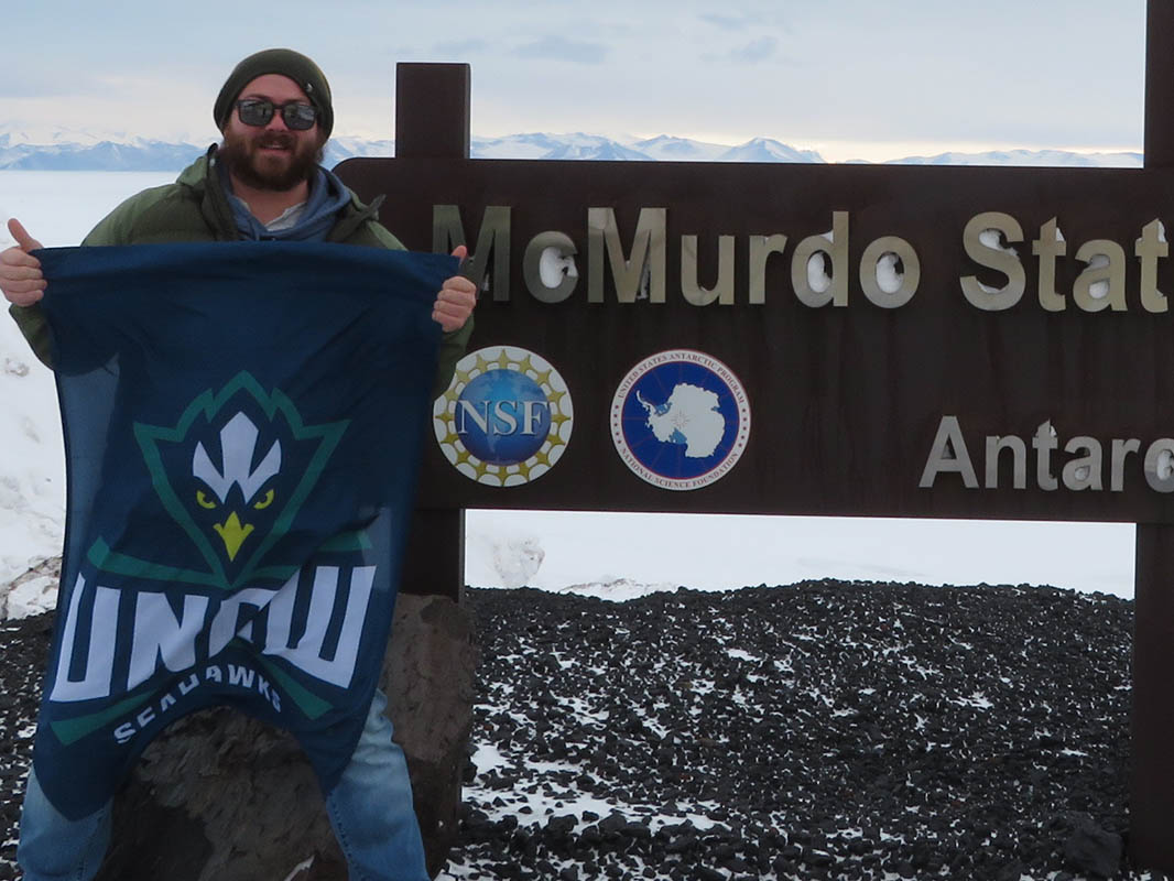 Maxwell Moody, in coat, hat and sunglasses, holds up a UNCW Seahawks blanket in front of the sign at McMurdo Station, Antarctica.