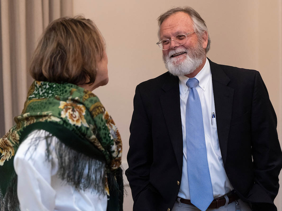 CHHS Dean Charlie Hardy (right) talks to Janet Burkholder (left), a member of the Nurse Advocate Board. Her back is turned and she wears a large, green-and-gold scarf with black fringe.