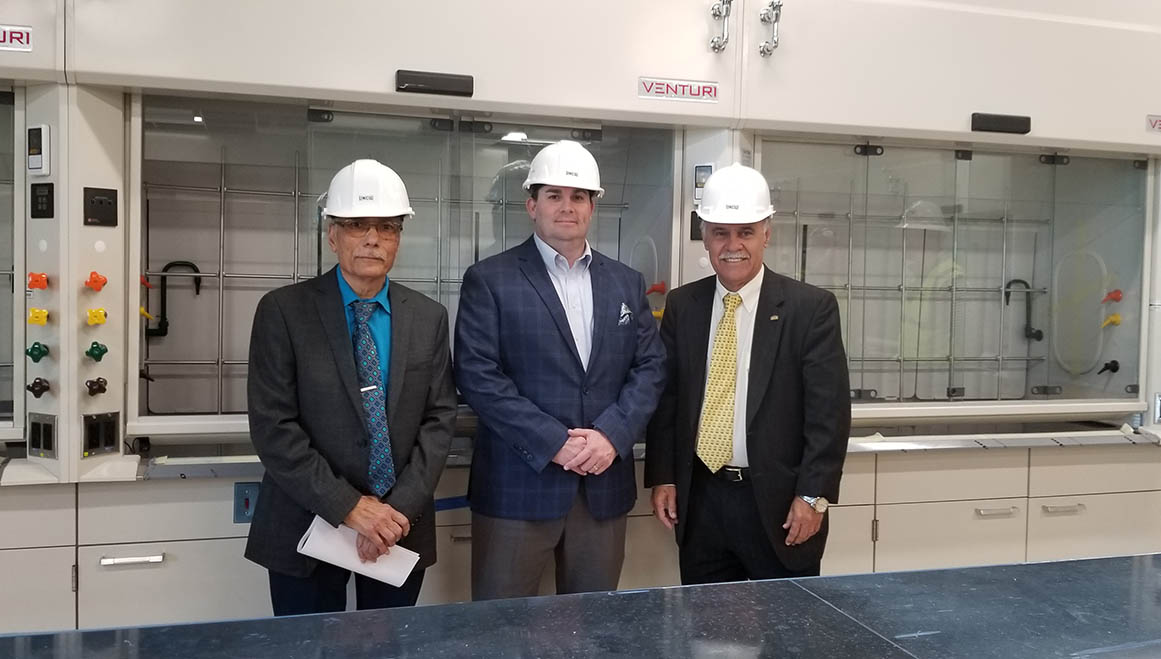 Left to Right: Dr. Yousry Sayed, N.C. House Majority Leader John Bell IV '01 and Chancellor Sartarelli, in suits and hard hats, stand in one of the labs inside Veterans Hall, which will open later this year.