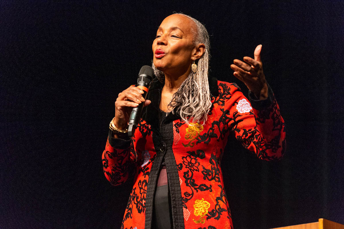 Susan L. Taylor, eyes closed, holding microphone in her right hand and gesturing with her left hand. Her outfit is colorfuland her expression soulful.