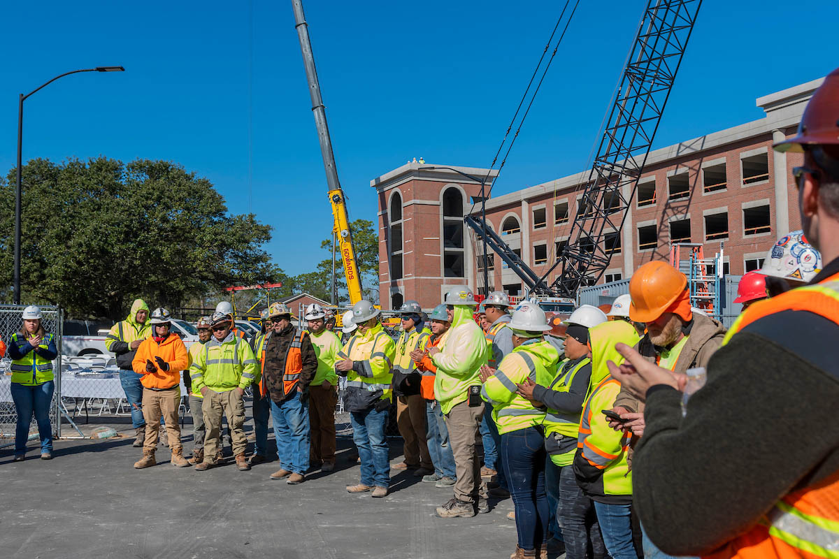 A group of construction workers stand in front of a crane and the new parking deck.