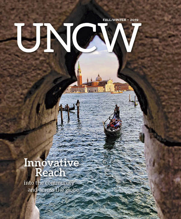 UNCW Magazine: Image is a gondola passing under an archlike structure on a canal in Venice.