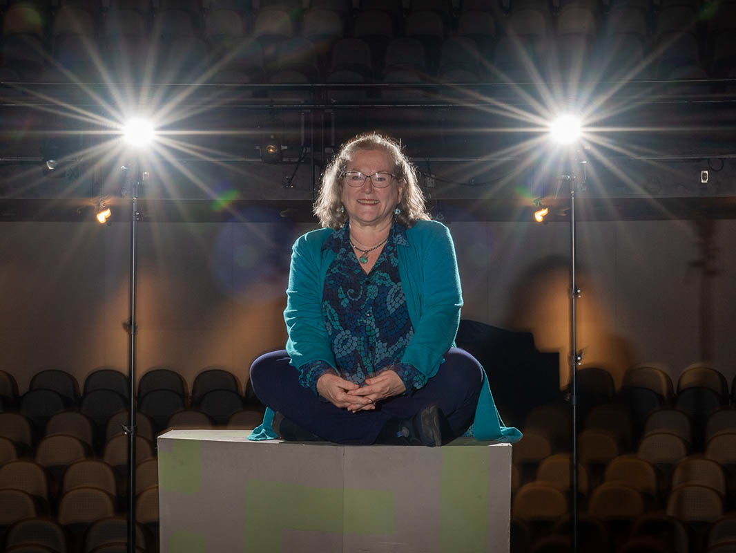 Susan Wilder sitting atop a set piece in the theatre in the Cultural Arts Building