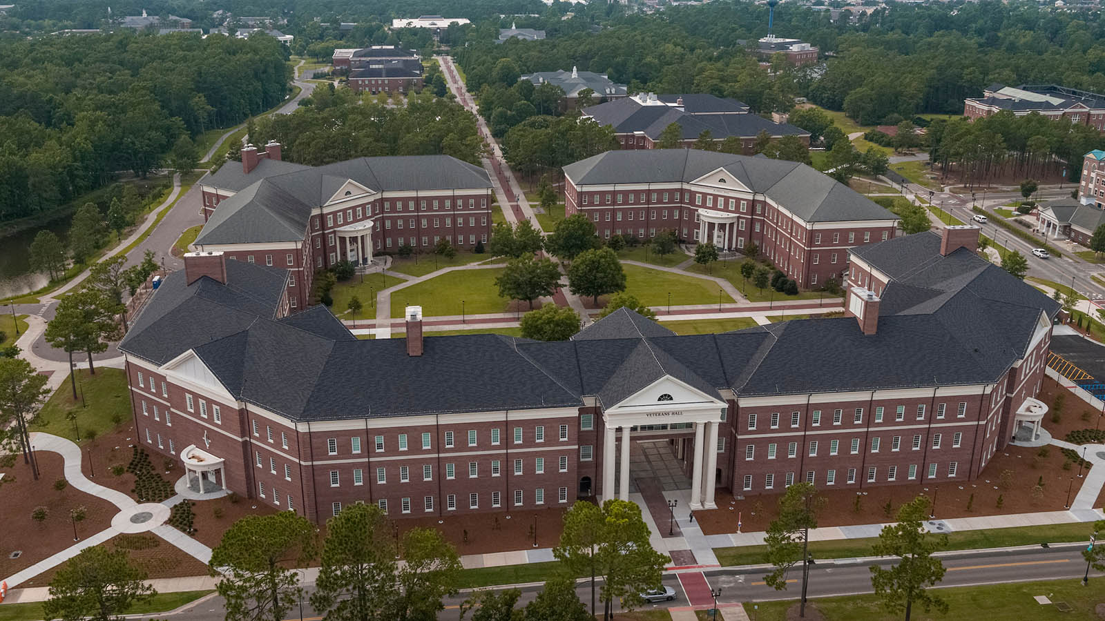 Photo of the quad that includes the Teaching Lab (back left), McNeill Hall (back right) and the newly completed Veterans Hall (foreground). Photo was taken by a drone on the side that faces Walton Drive. Chancellor's Walk runs through the quad and beyond toward the Clock Tower.