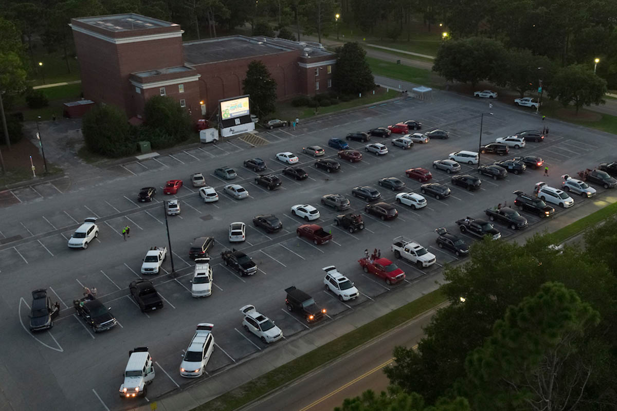 Aerial view of the Kenan Auditorium with dozens of cars parked there, and a freestanding movie screen at the side of the building.