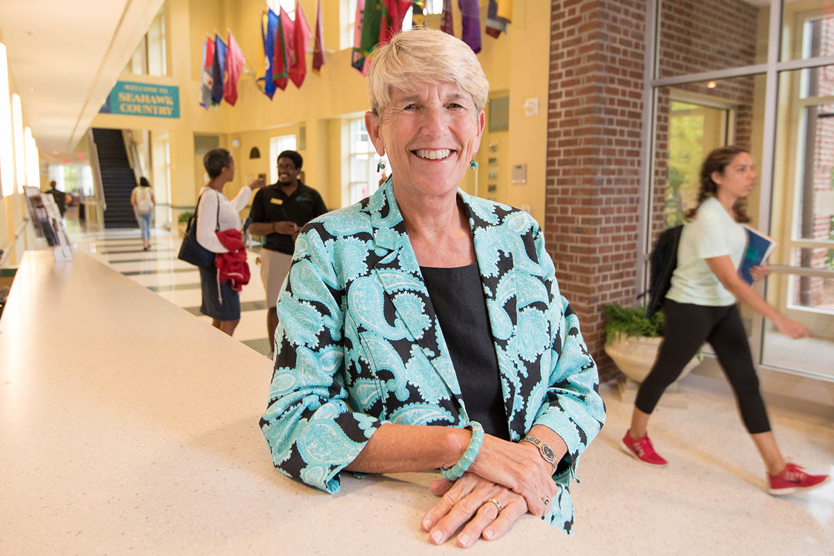 Portrat of Pat Leonard in a teal and brown ensemble standing at the service desk inside the Fisher Student Center, with students and staff walking and talking in the background.