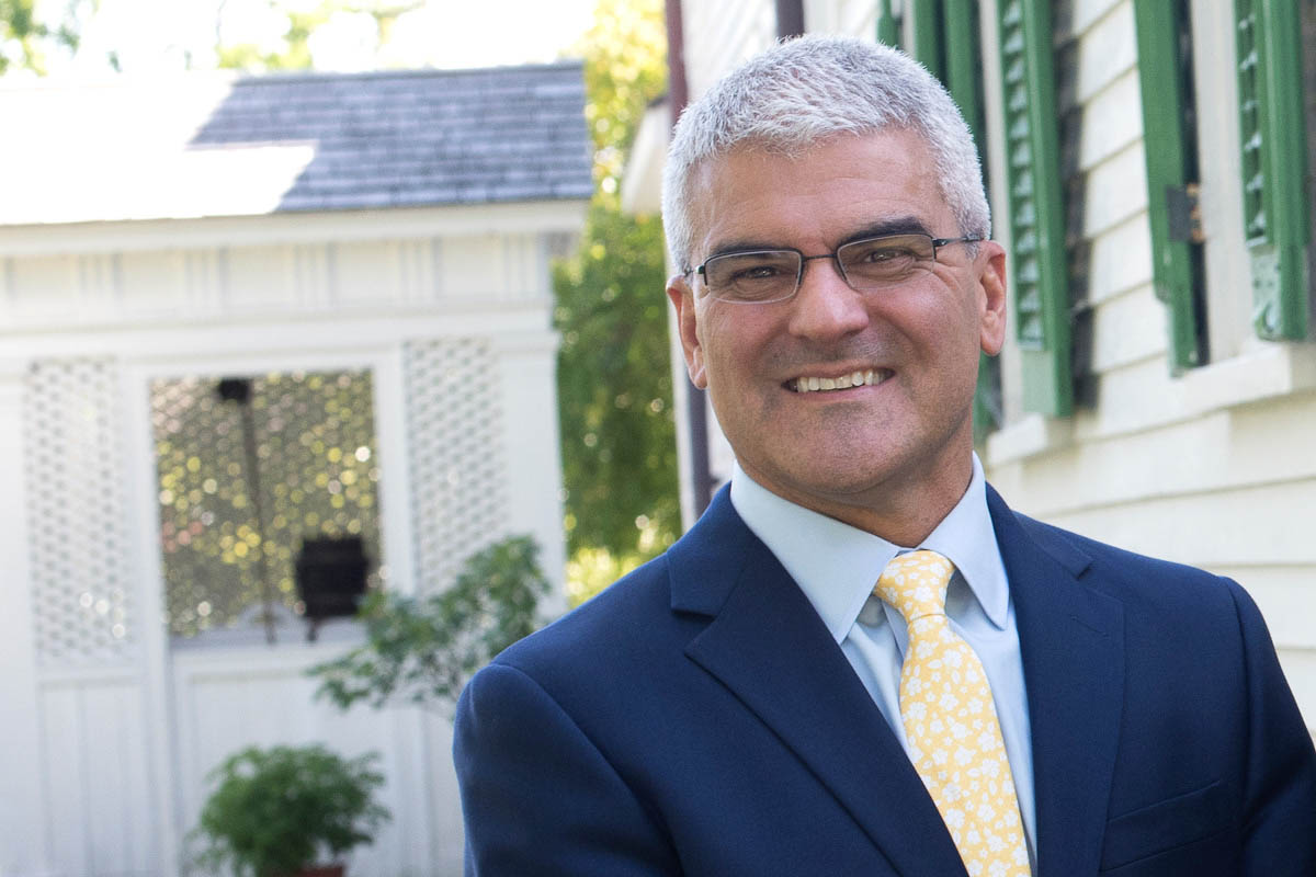 Portrait of James J. Winebrake in a navy blue suit jacket, light blue button-down shirt and yellow tie in front of a house.