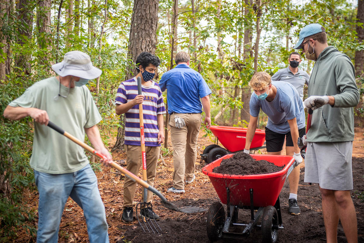 A group of volunteers with shovels and wheelbarrows works in the Bluethenthal Wildflower Preserve.