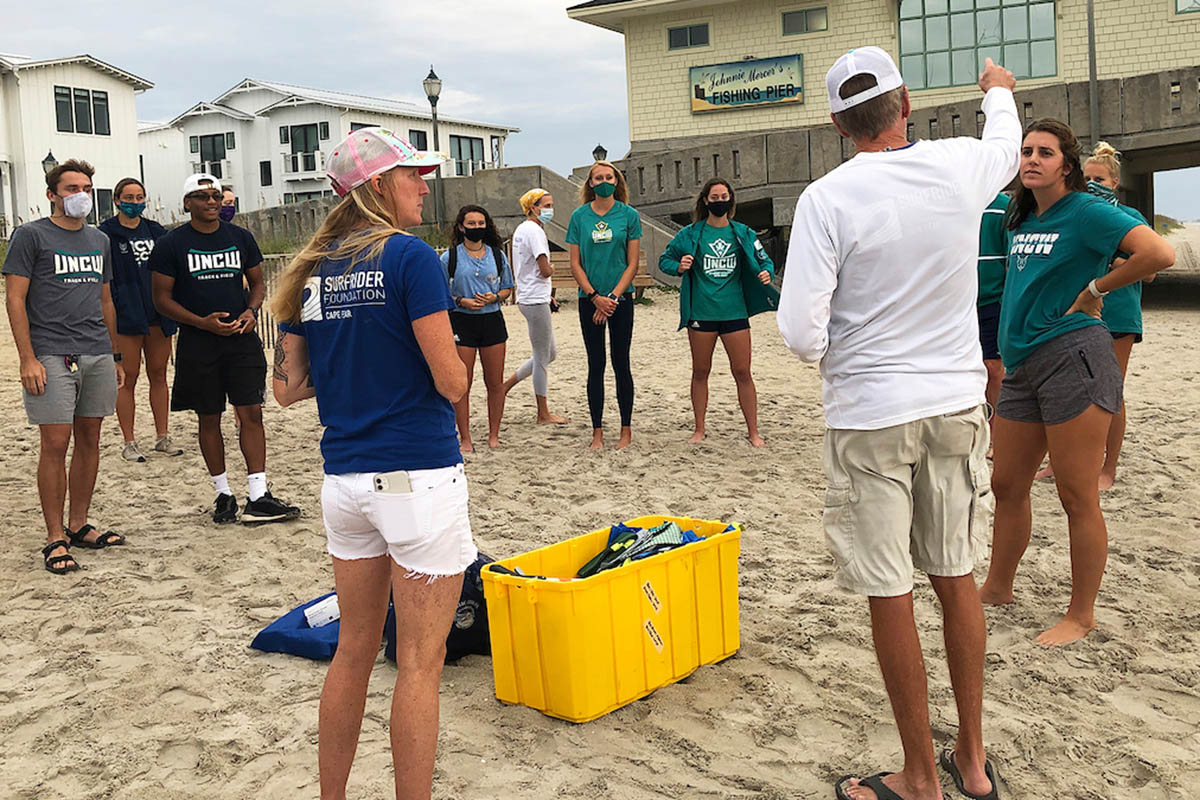 UNCW student-athletes stand on the beach awaiting instructions for where to clean up.