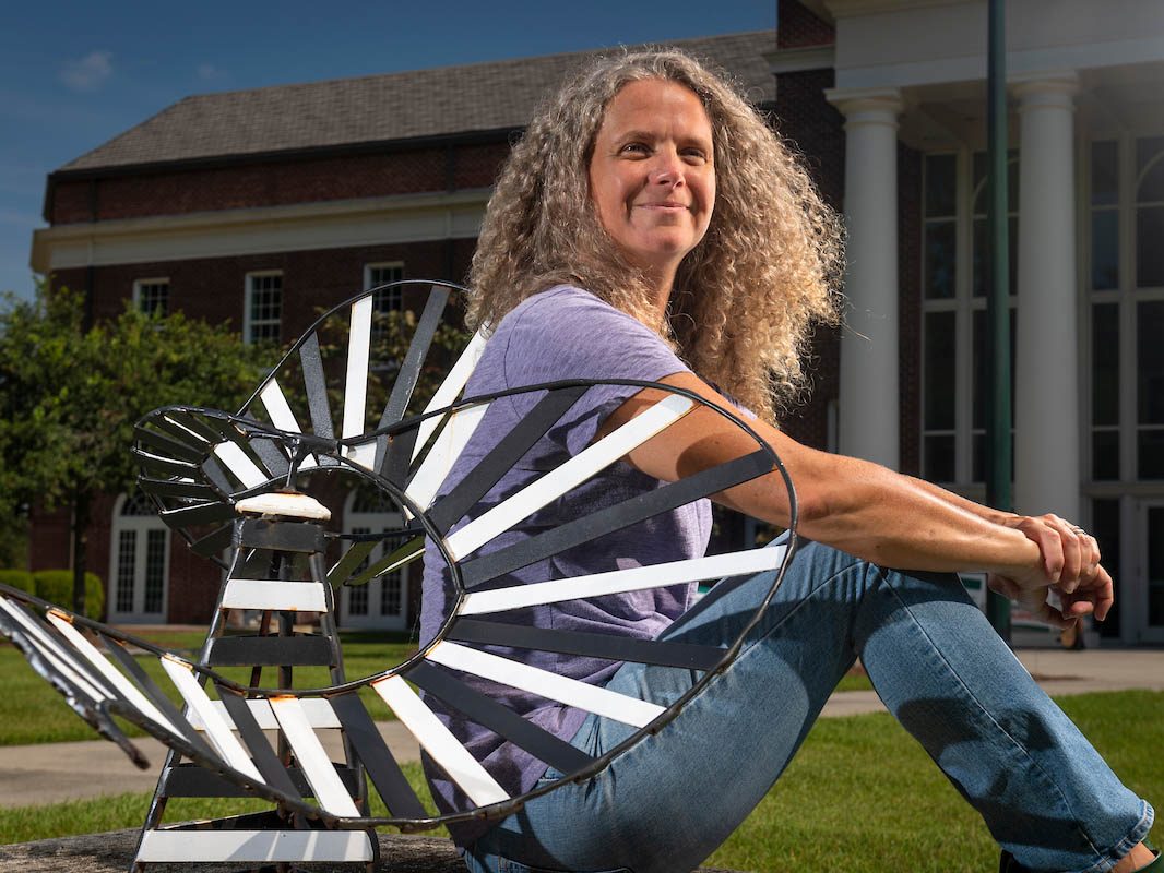 Andi Steele sits near a sculpture in front of the Cultural Arts Building.