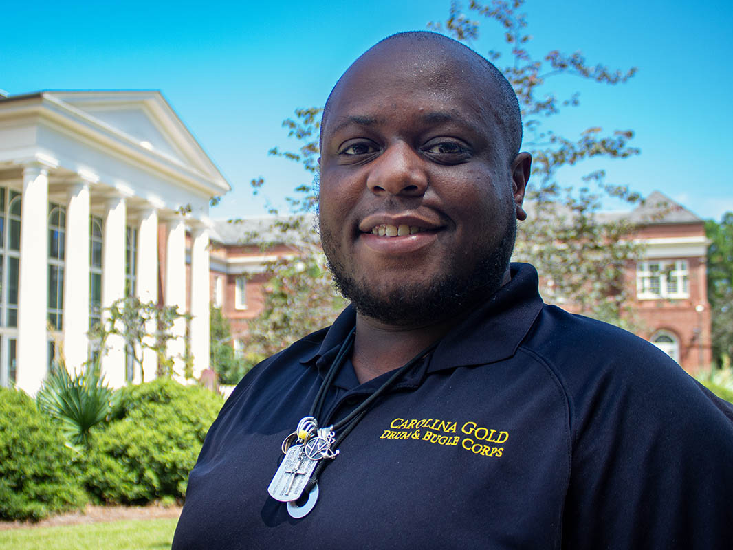Kennith Watts Jr. in a Carolina Gold Drum & Bugle Corps shirt, standing in front of the Cultural Arts Building.