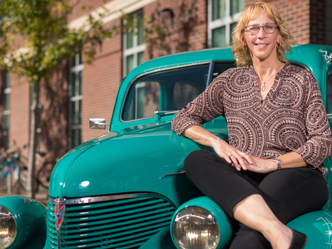 Heather Ianucci sits on top of her classic teal car.