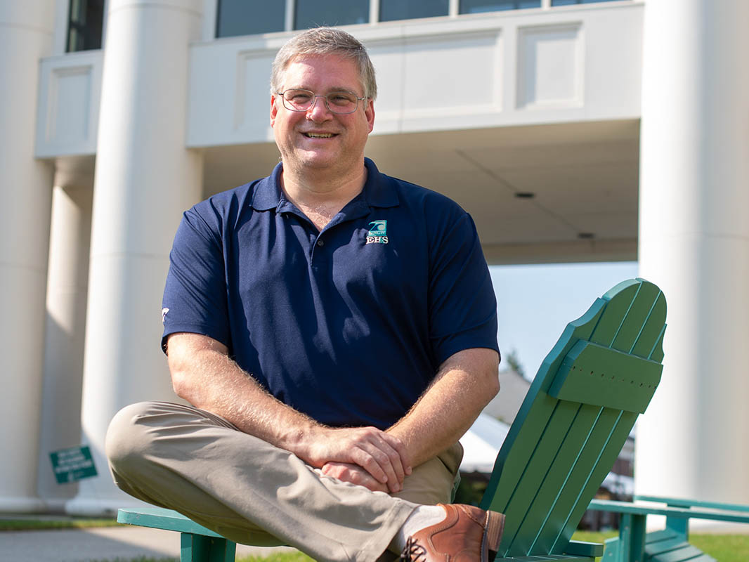 Jeff Campbell seated on an Adirondack chair in the Fisher student complex.