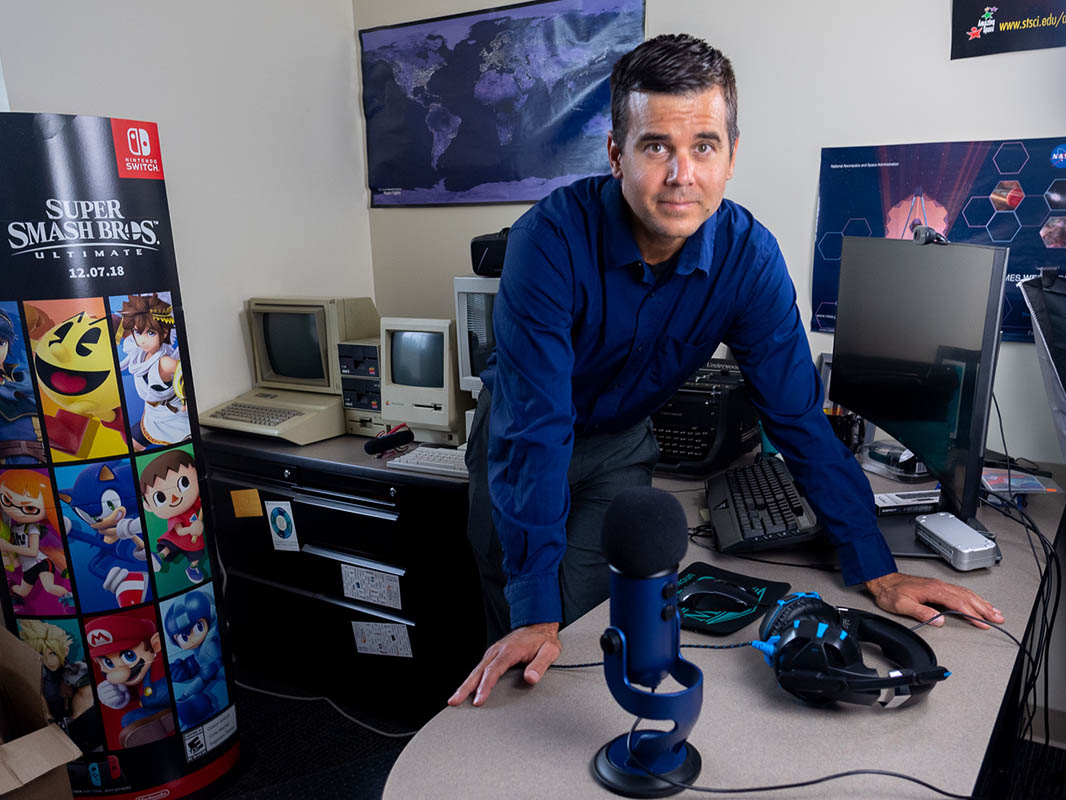 Ray Pastore leans over his desk, which contains some of the equipment he uses for his eSports courses.
