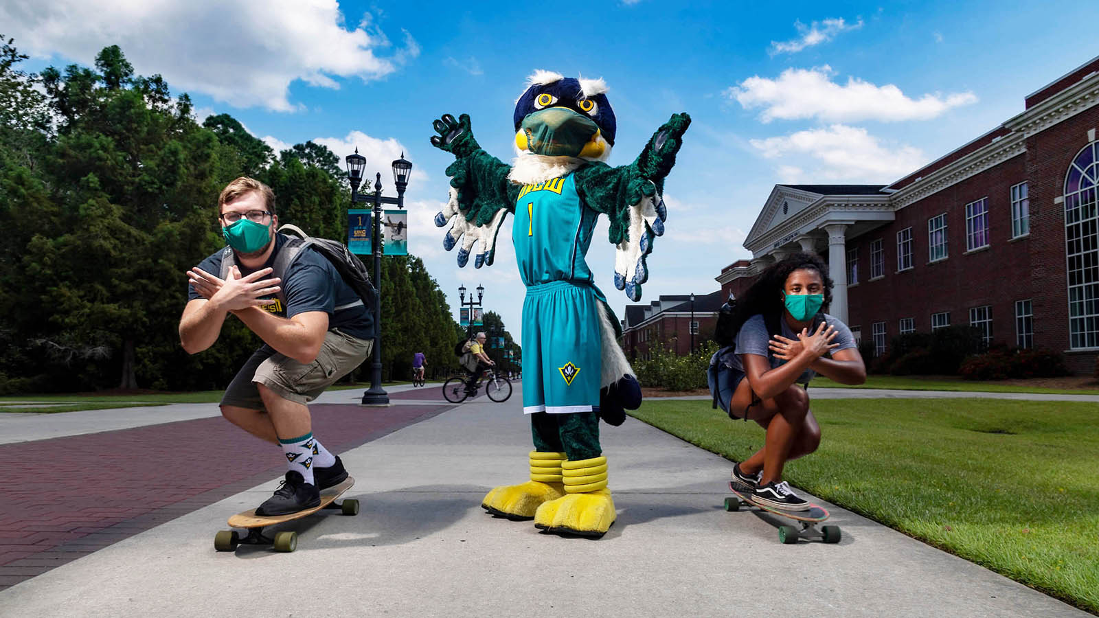 Sammy C. Hawk (center) is surrounded by two crouching skateboarders on Chancellor's Walk.