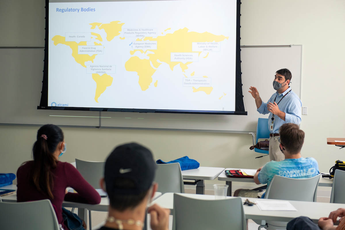 Alcami scientist Todd Doroski 'XX, in front of a screen with a map of the world listing regulatory bodies, delivers a guest lecture to Robert Williamson's Pharmaceutical Analysis class.