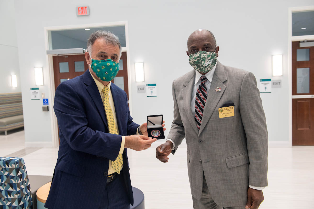 Chancellor Sartarelli, in mask and holding box with a medallion, stands next to retired Lt. Gen. Walter Gaskin, who serves as secretary of the NC Department of Military and Veterans Affairs.