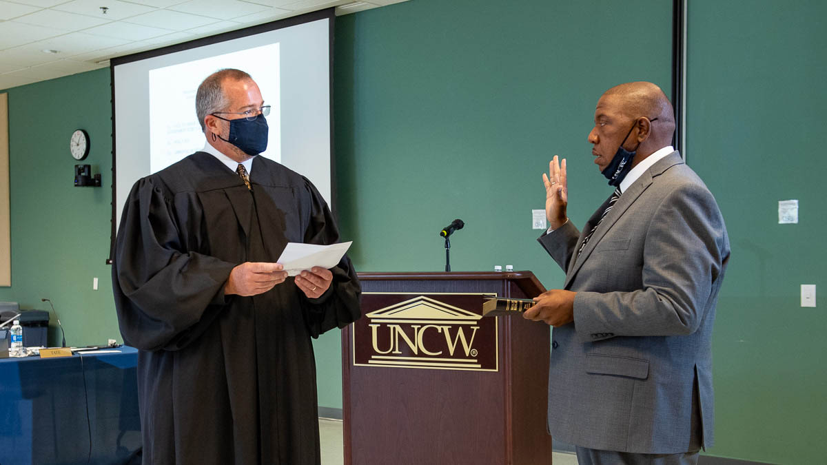 District Court Judge Kent Harrell (left) administers the oath of office to new UNCW Board of Trustees memberJimmy Tate (right, with hand raised ) on Thursday, April 29. Tate was appointed to replace Michael Lee, who was elected to the North Carolina State Senate.
