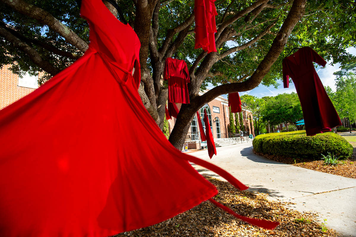 Red dresses hang from trees near Randall Library.